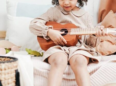 a-girl-in-ackecked-long-sleeve-dress-playing-brown-acoustic-3662767